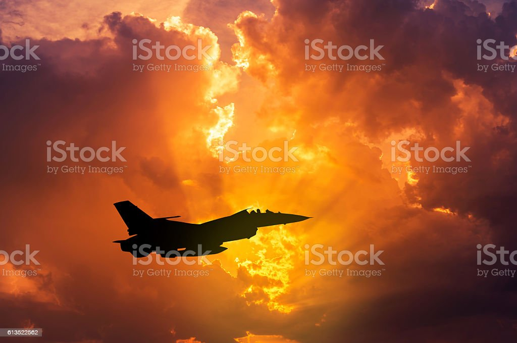 silhouette F-16 military aircraft flying on sunset stock photo