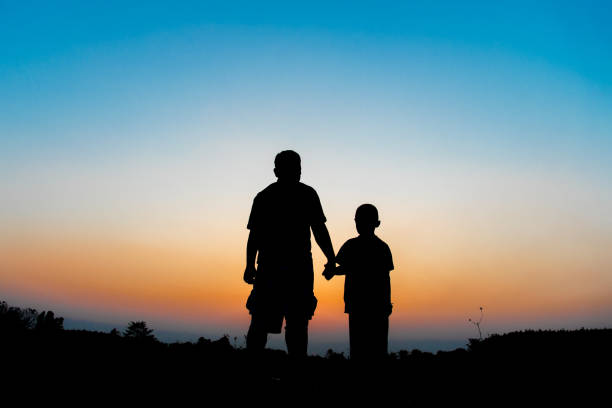 Silhouette Father and son hold hands in evening time stock photo