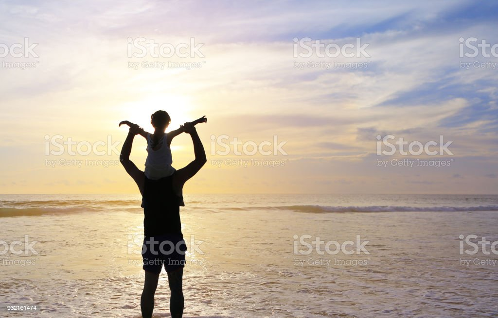 Silhouette father were riding neck carries daughter look out at the sea at sunset. stock photo