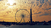 Paris, France - May 11, 2017: Sunrise traffic at Place de la Concorde with Egyptian Obelisk and Ferris Wheel in Paris, France