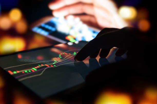 Dedo de silueta en tableta con gráfico bolsa comercio pantalla con Resumen blur smartphone fondo bokeh, concepto de mercado de valores - foto de stock