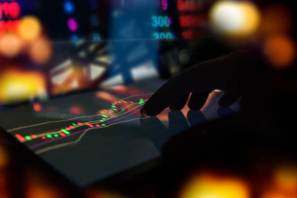 Silhouette finger on tablet with technical graph trading screen with abstract blur smartphone bokeh background , stock market concept stock photo