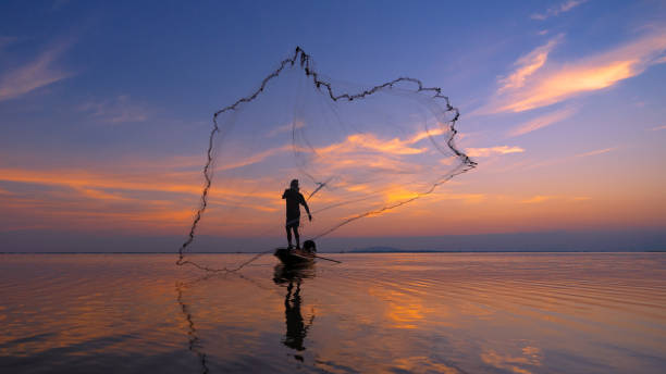 Silhouette Fisherman fishing nets on the boat. Silhouette of fishermen using coop-like trap catching fish in lake with beautiful scenery of nature morning sunrise. Silhouette Fisherman fishing nets on the boat. Silhouette of fishermen using coop-like trap catching fish in lake with beautiful scenery of nature morning sunrise. fishing net stock pictures, royalty-free photos & images