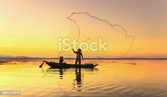 istock Silhouette fisherman on fishing boat setting net with sunrise 664213078