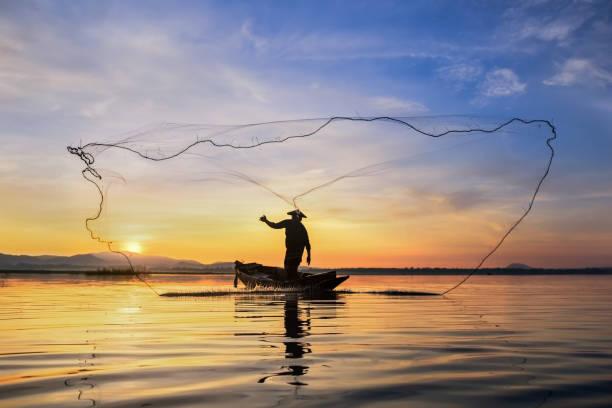 silhouette fisherman on fishing boat setting net with sunrise - oceano pacifico foto e immagini stock