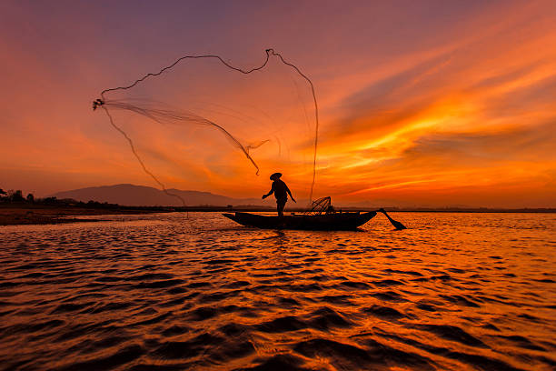 Silhouette fisherman with net at the lake in Thailand Silhouette fisherman with net at the lake in Thailand netting stock pictures, royalty-free photos & images