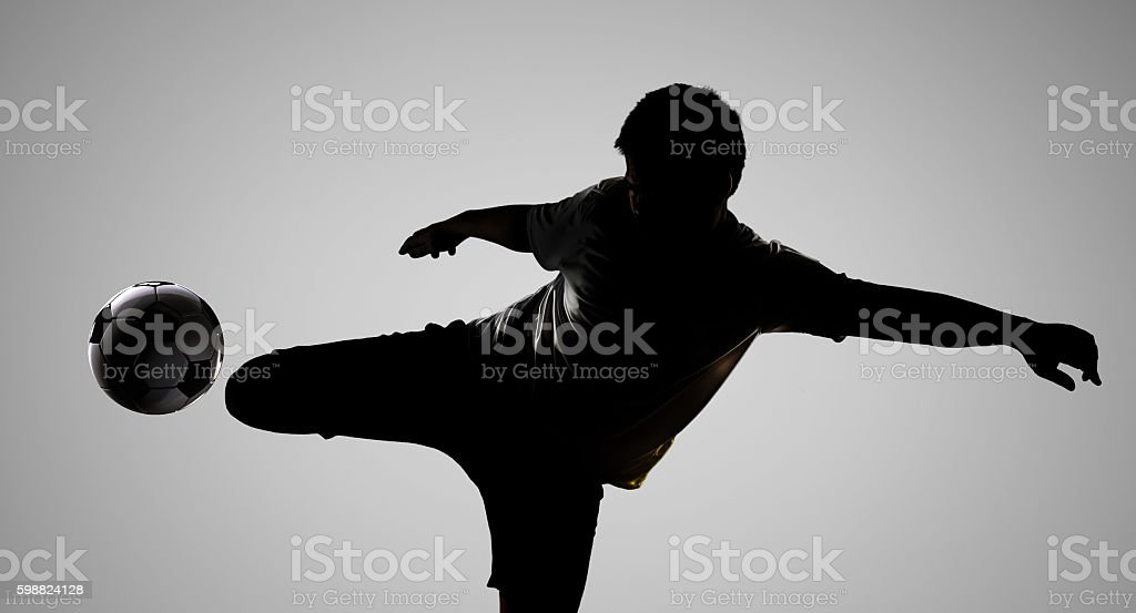 silhouette football player kicking the ball stock photo