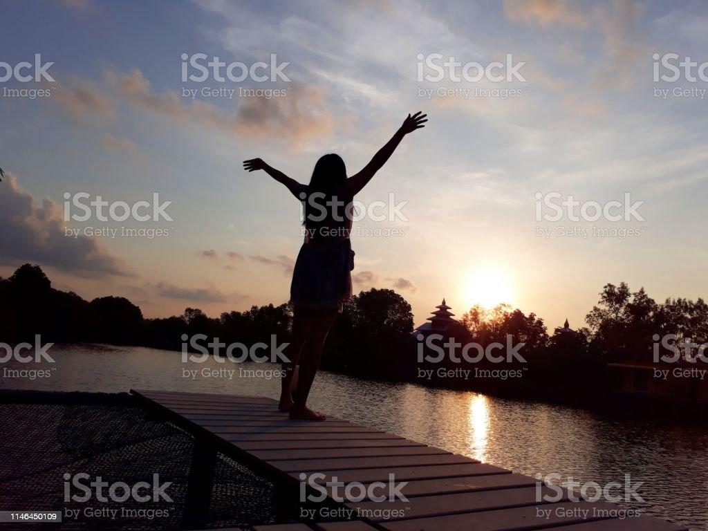 朝の日差しの下で美しい風景の景色と木製の橋の上にシルエットの女の子