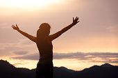 silhouette girl standing on mountain and rise up her hand with sunlight