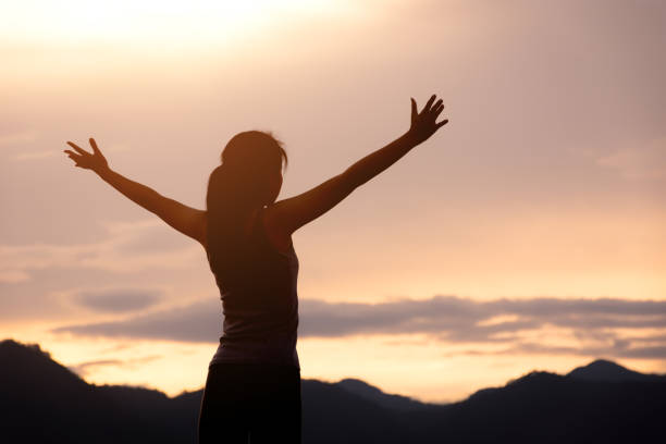 silhouette girl standing on mountain and rise up her hand stock photo