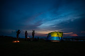 Silhouette  group of Asian friends tourist drinking and playing guitar together with happiness in Summer while having camping near lake