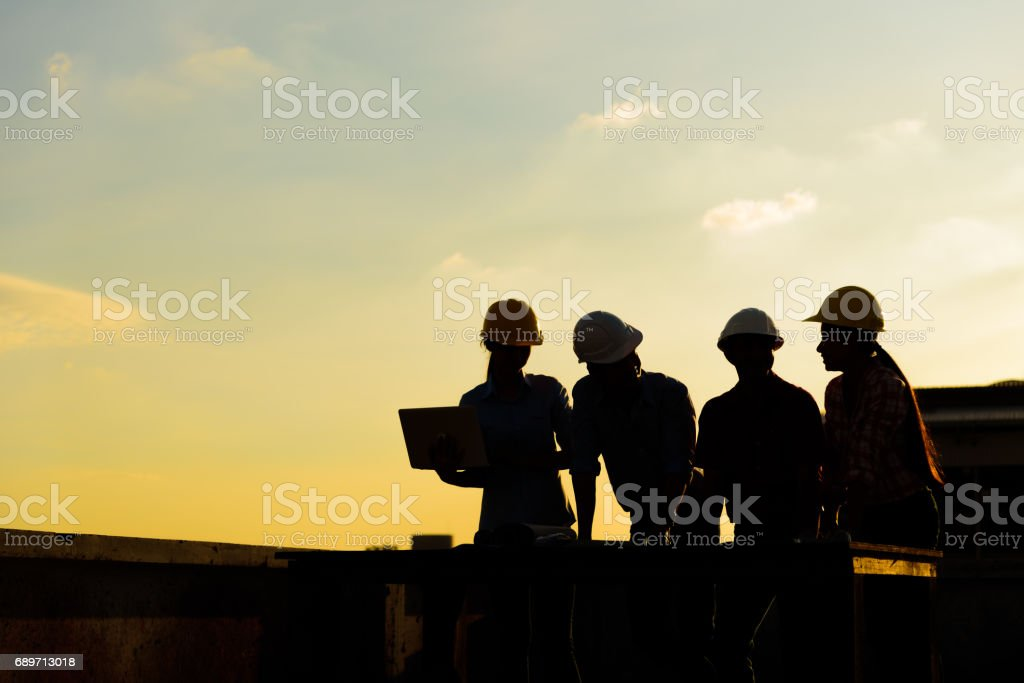Silhouette Group of Engineers meeting on top of terrace in sunset time stock photo