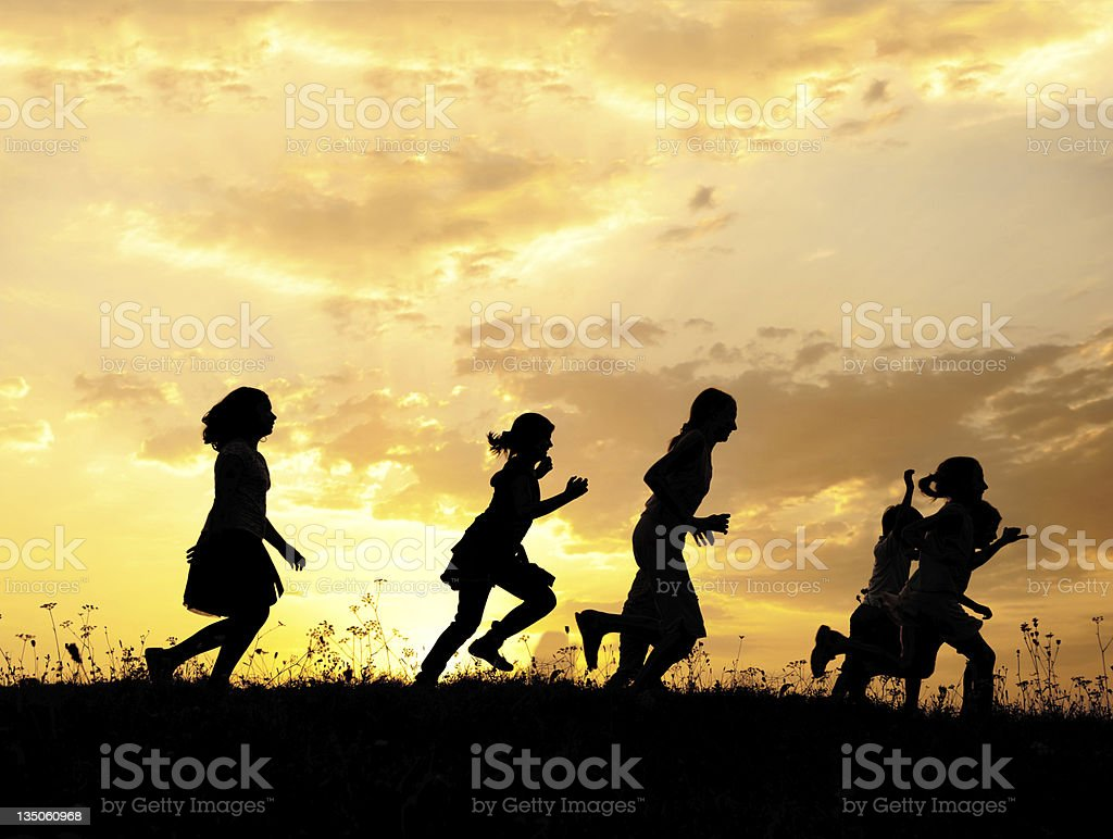 Silhouette, group of happy children playing on meadow, sunset, s royalty-free stock photo