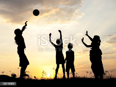 istock Silhouette, group of happy children playing on meadow, sunset, s 135190831