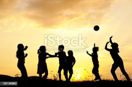istock Silhouette, group of happy children playing on meadow, sunset, s 135190862