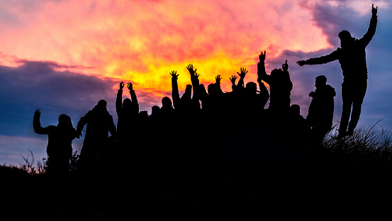 Silhouette, group of happy people jumping in sunset - image
