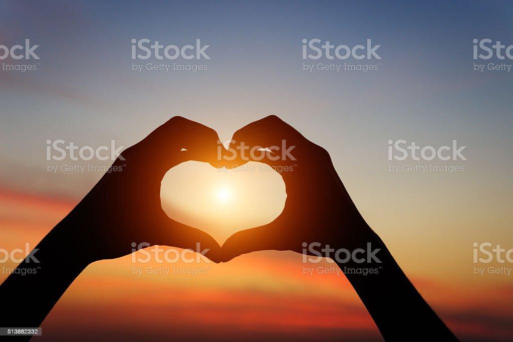 Silhueta de mão gesto sensação amor durante o pôr-do-sol - foto de acervo