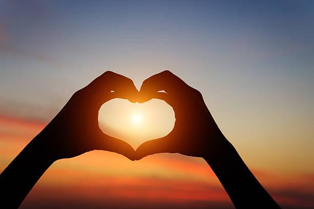 Silueta de mano gesto sensación de amor en la puesta de sol - foto de stock
