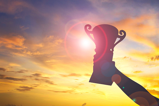 istock silhouette hand hold trophy and sunset background 1143845338