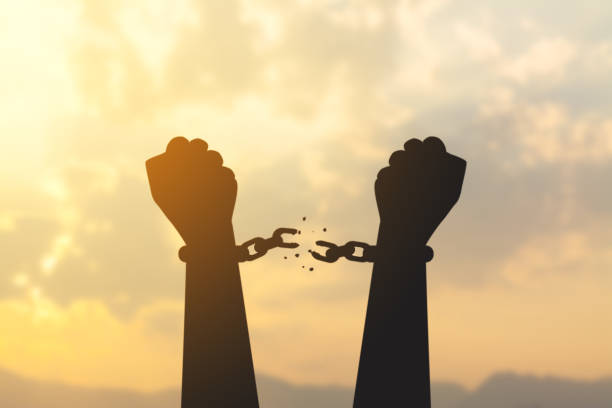 silhouette hand with chain is absent silhouette hand with chain is absent and blurred sky in sunrise background freedom stock pictures, royalty-free photos & images
