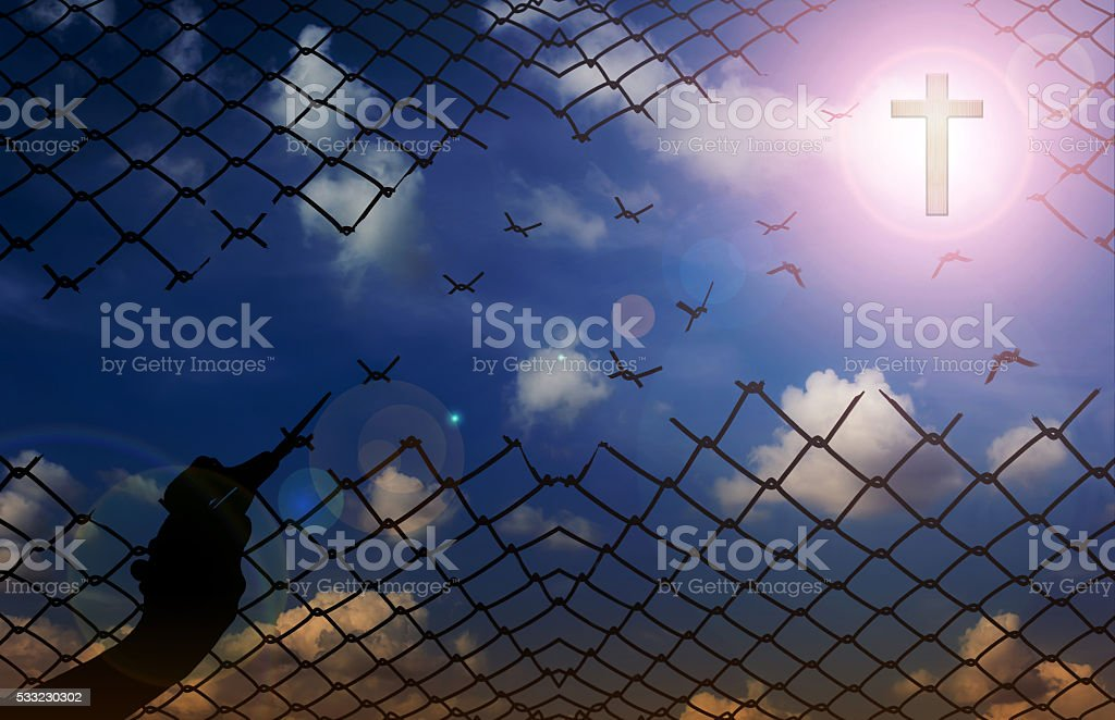 Silhouette hand with scissors cutting net with sky background, f stock photo