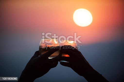 Two female hands holding glasses with drinks celebrating a toast sundowners at sunset high above the clouds Cape Town South Africa