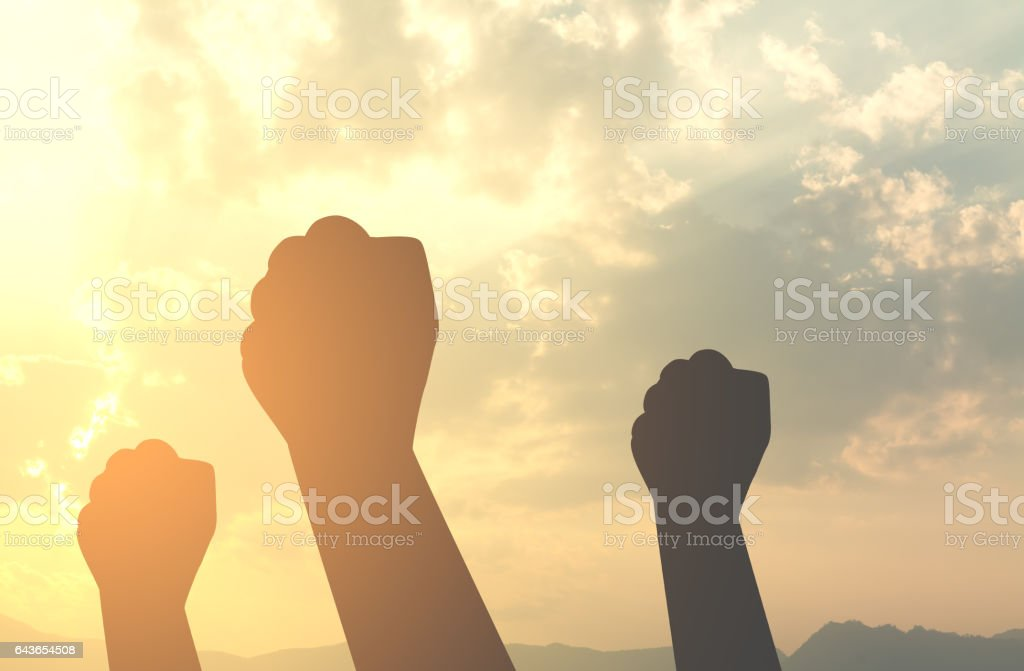silhouette hands fist with sun lighting stock photo