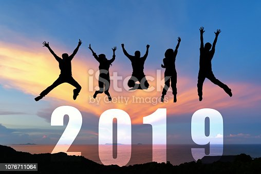 istock Silhouette happy business teamwork jumping congratulation graduation in Happy New year 2019. Freedom lifestyle group people jump as part of Number 2019 at the sunset beach 1076711064