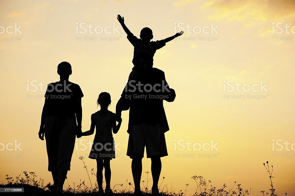 Silhouette, happy children with mother and father, family at sun stock photo