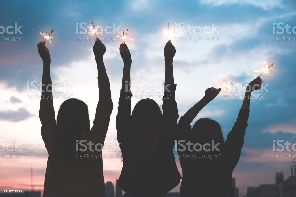 silhouette happy group of asia girl friends enjoy and play sparkler at rooftop party at evening sunset,Holiday celebration festive,teeage lifestyle,freedom and fun stock photo
