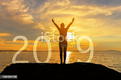 istock Silhouette happy woman relax for congratulation graduation in Happy New year 2019. Freedom lifestyle woman as part of Number 2019 at the sunset beach, copy space. 1084554156