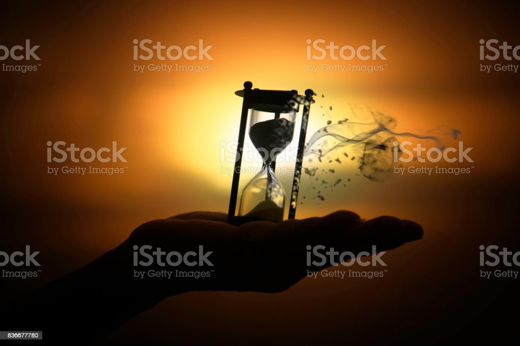 Silhouette hourglass is disintegrating on hand Pocket watch at last sunlight stock photo