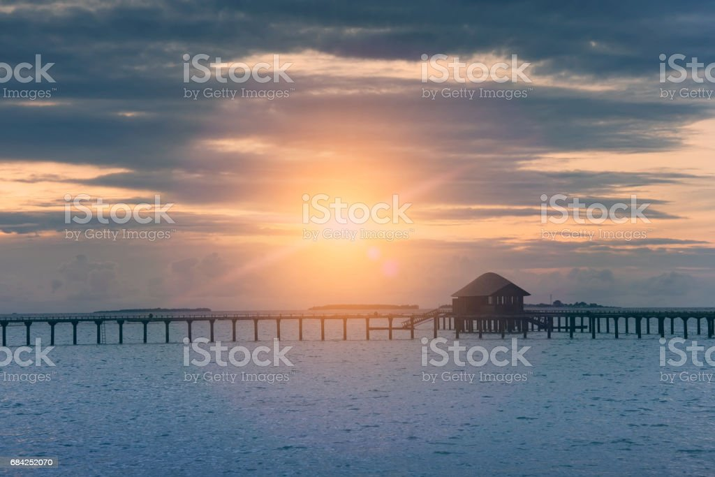 Silhouette hut over the transparent quiet sea water  on a sunset, toning. Maldives royalty-free stock photo