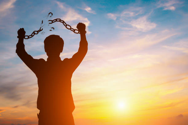 Silhouette image of a businessman with broken chains in sunset stock photo