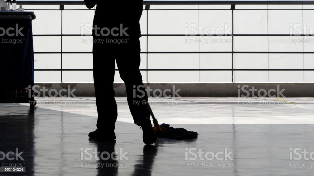 Silhouette image of cleaning service people sweeping floor with mop stock photo