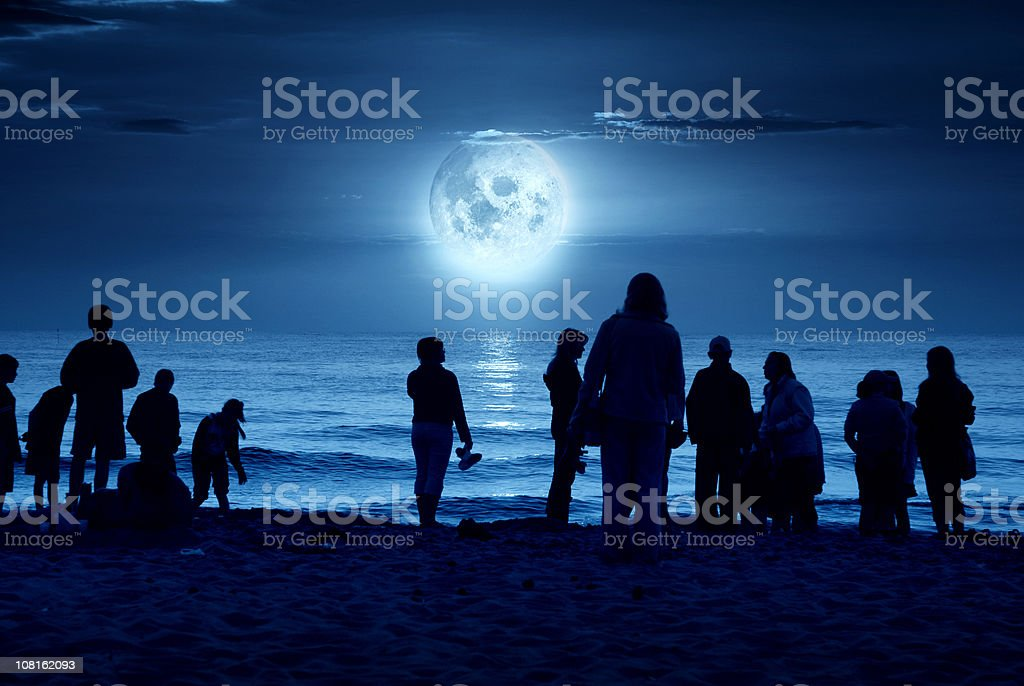 Silhouette Image of People Standing on Moonlit Beach royalty-free stock photo