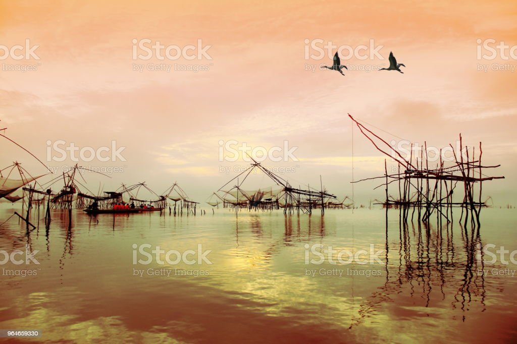 Silhouette image of thailand style Fish traps. fish trap consisting of a long net laid across part of the river and the fisherman on the boat and colorful birds and sky background royalty-free stock photo
