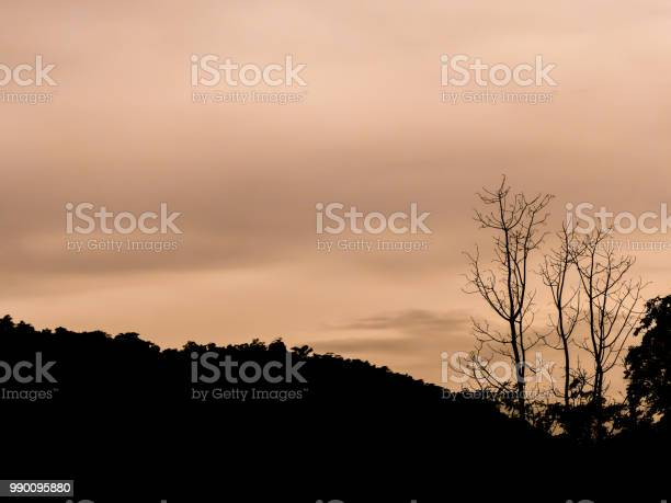 Photo of silhouette image - sunlight behind the mountain at sunrise