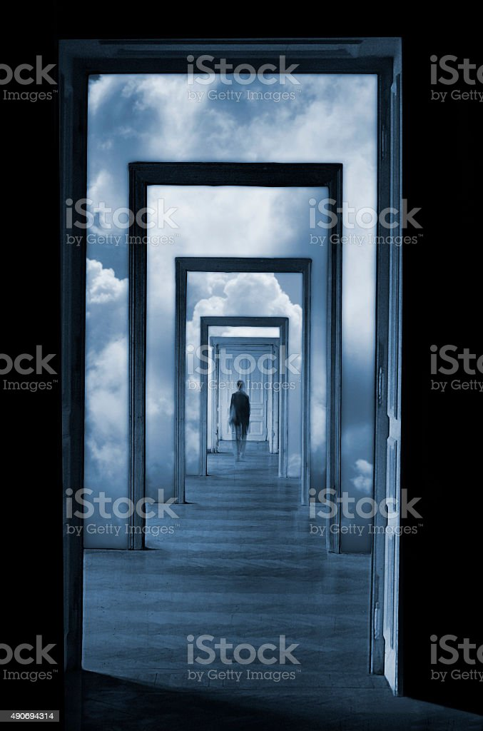 Silhouette in a dreamlike corridor with many doors. stock photo
