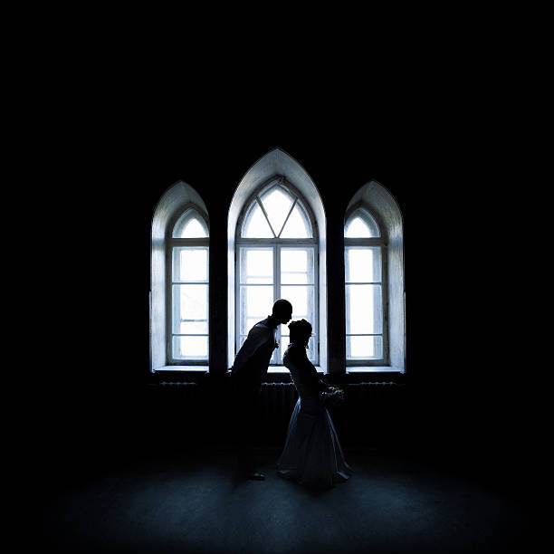 silhouette kissing couple near the vintage window stock photo