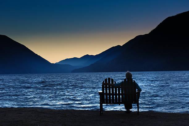 silhouette lonely woman sitting watching the sunrise - veuve photos et images de collection