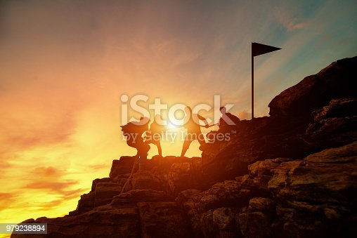 Silhouette male and female hikers climbing up mountain cliff, Helps and team work concept.