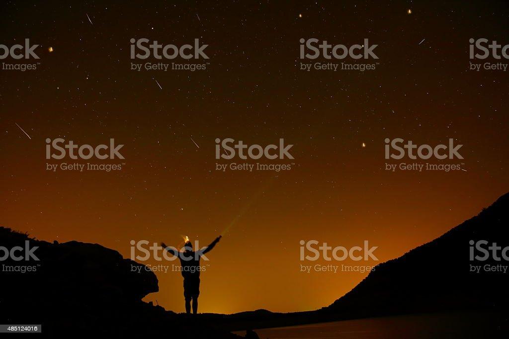 silhouette man arms raised into stars sky stock photo