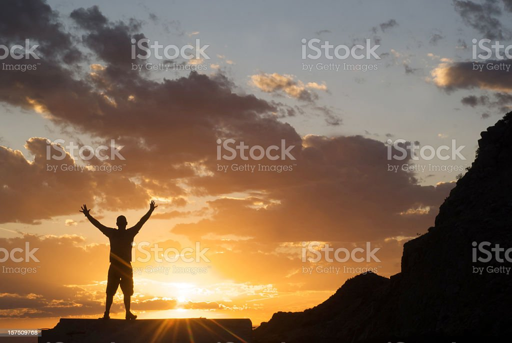 silhouette man arms raised into sunset sky royalty-free stock photo