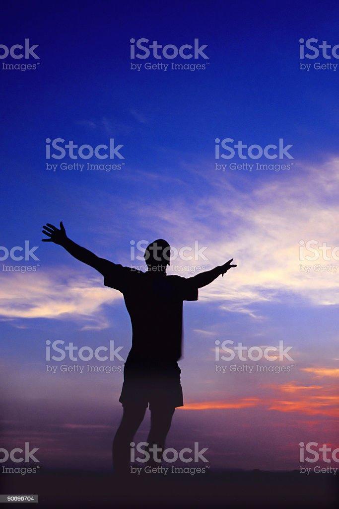 silhouette man arms raised into sunset sky royalty-free stock photo