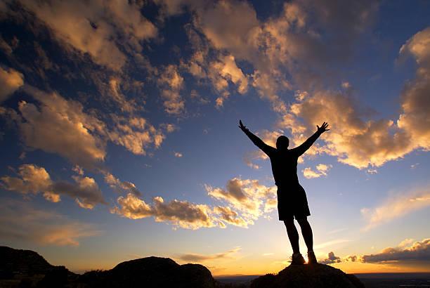 silhouette man arms raised sunset sky landscape stock photo