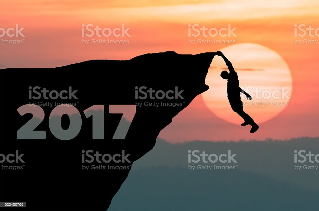 Silhouette Man climbs into cliff of Happy New Year 2017 stock photo