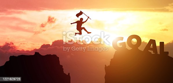 Silhouette man hand hold flag jumps from mountain to the word GOAL with sky, clouds and sunset background. Fight for reach key performance indicator in summer with copy space for label text banner