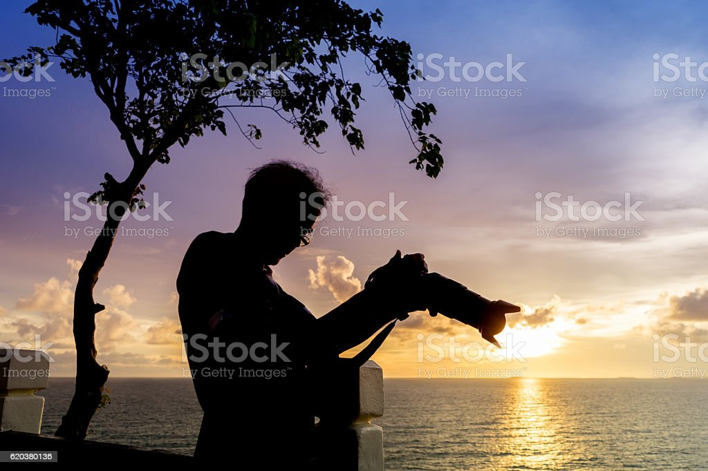Silhouette man holding camera beside sunset sea. zbiór zdjęć royalty-free