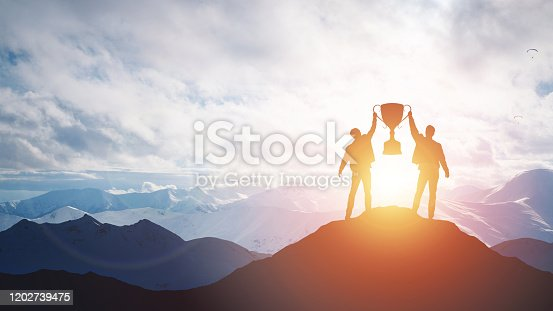 Silhouette man holding up a gold trophy cup. Vicotory concept